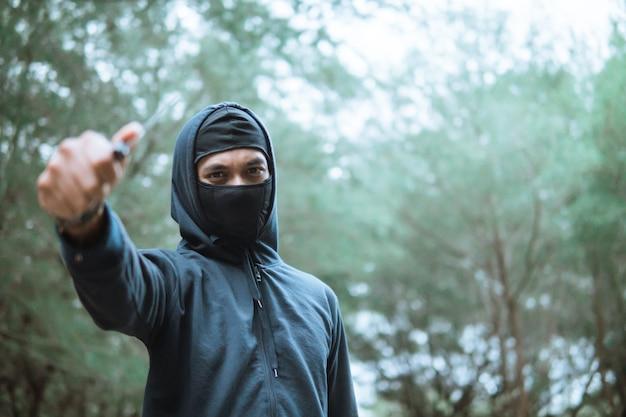 De dief in een masker en een zwarte hoodie droeg het mes naast de copyspace toen hij in het bos stond