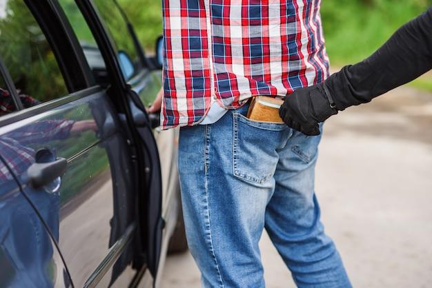 De dief in zwarte kleding en handschoenen stelen van een portemonnee met geld uit zak bij de auto. zakkenrollen op straat overdag.