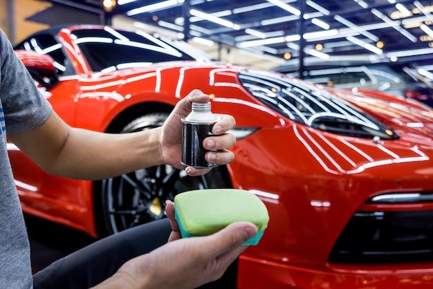 De dienstarbeider die van de auto nanodeklaag op een autodetail toepast