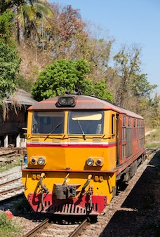 De dieselelektrische locomotief staat geparkeerd bij een klein treinstation op de top van de hoge berg na ondersteuning om een sneltrein naar het station te maken, vooraanzicht op de achtergrond.