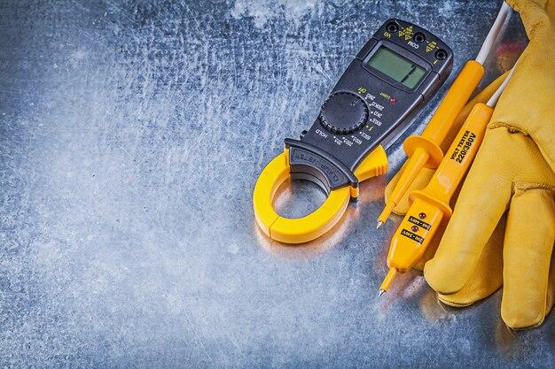 De digitale beschermende handschoenen van het ampèremeter elektrische meetapparaat op metaaloppervlakte, elektriciteitsconcept