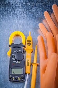 De digitale rubberhandschoenen van de ampèremeter elektrische meetapparaatelektriciens op metaallijst, elektriciteitsconcept