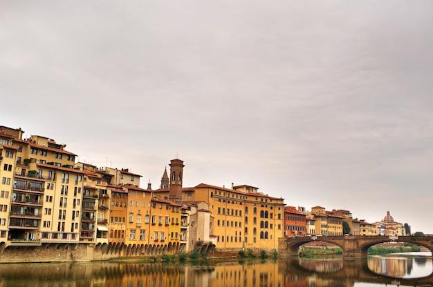 De dijk en de brug van de heilige drie-eenheid van de ponte santa trinita op de rivier de arno in florence. italiaans.