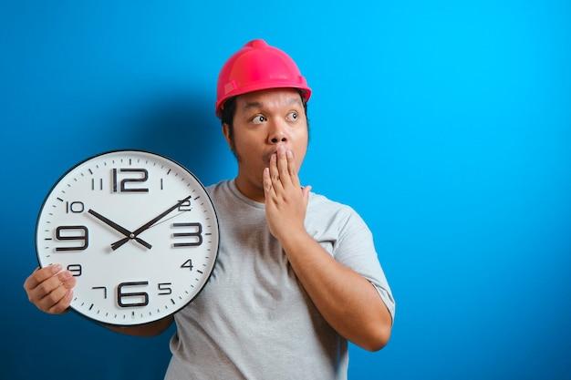 De dikke aziatische man met een helm die een klok vasthoudt met een verbaasde uitdrukking omdat hij te laat op zijn werk was