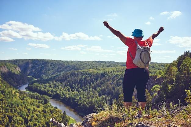 De dikke vrouw hief haar handen omhoog en verheugde zich op de berg. het concept van overwinning op zichzelf, motivatie, karaktersterkte. een prachtig panoramisch uitzicht op een bergrivier