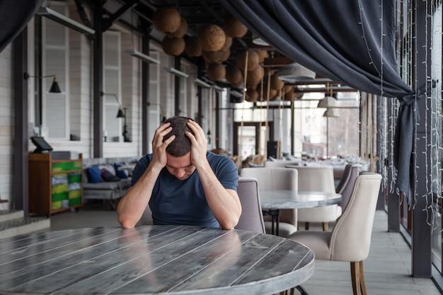 De directeur van het restaurant van de man houdt zijn hoofd vast, voelt zich bezorgd en depressief
