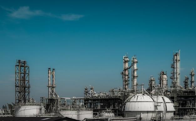 De distillatietoren van het gas en gasopslagtanks van aardolie industrieel op blauwe hemel