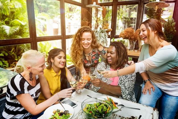 De diversiteitsvrouwen groeperen hangend het eten samen concept