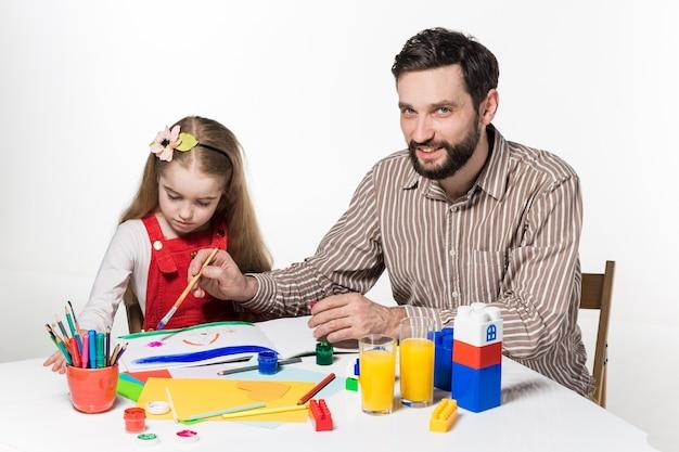 De dochter en vader tekenen en schrijven samen op witte achtergrond