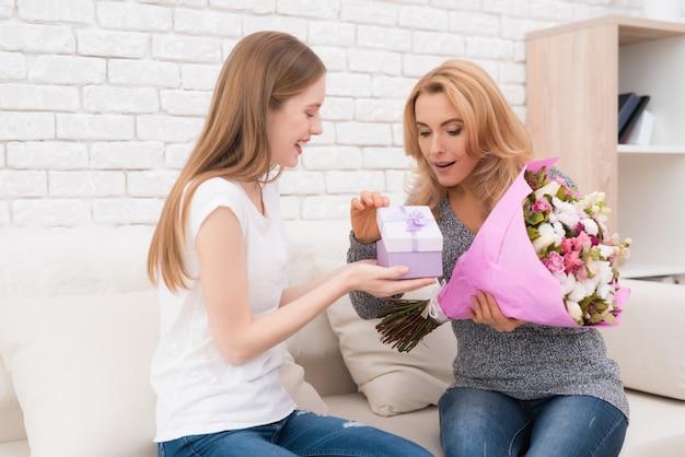 De dochter geeft haar moeder bloemen en cadeautjes.