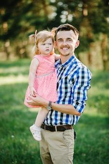 De dochter knuffelt vader op de natuur op zomervakantie. papa en meisje spelen in het park bij zonsondergang. concept van vriendelijke familie. detailopname.