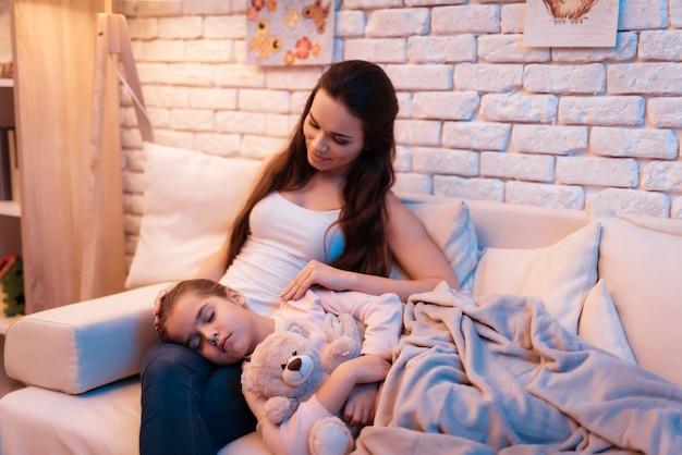 De dochter slaapt thuis op de schoot van de moeder laat in de nacht.