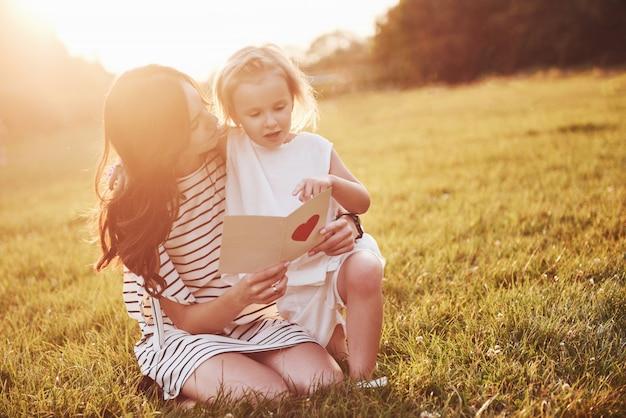 De dochter van het kind feliciteert haar moeder en geeft haar een ansichtkaart.