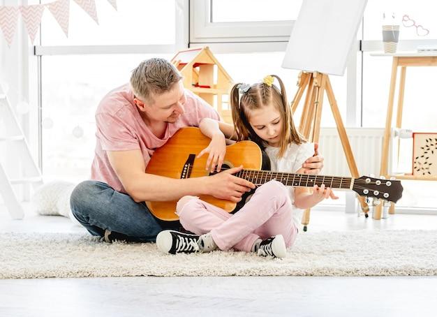 De dochter van het vaderonderwijs om gitaar te spelen