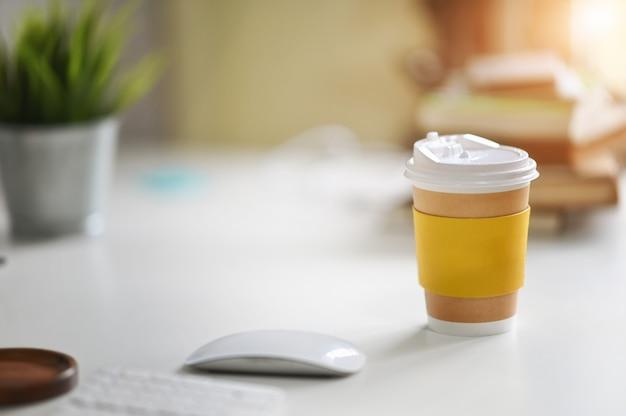 De document kop haalt koffie op bureaulijst weg in ochtendtijd.
