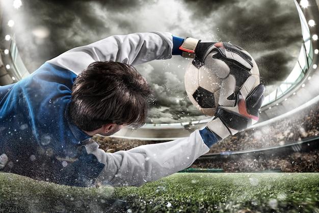 De doelman vangt de bal in het stadion