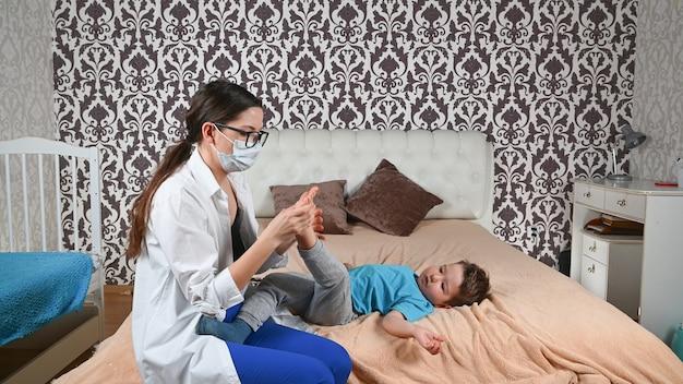 De dokter controleert de benen van het kind.