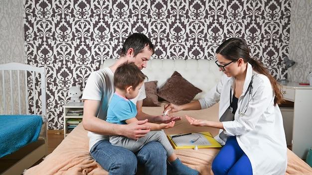 De dokter desinfecteert de handen van de vader met het kind.