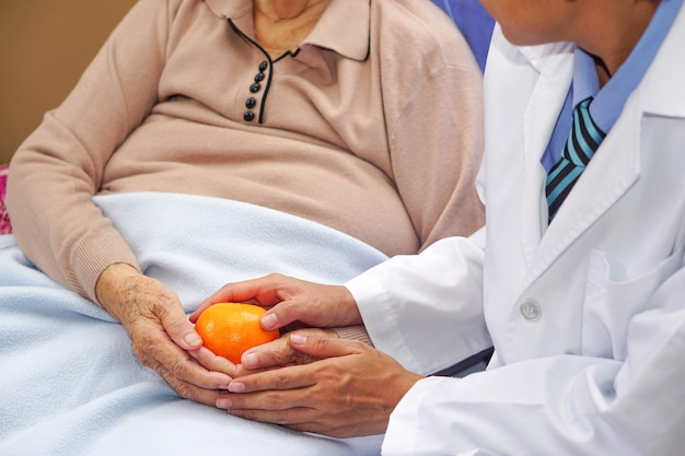 De dokter gaf de aziatische oudere of oudere oude vrouw een sinaasappel