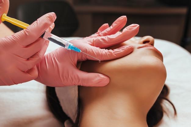 De dokter geeft een injectie in het jukbeen van de vrouw