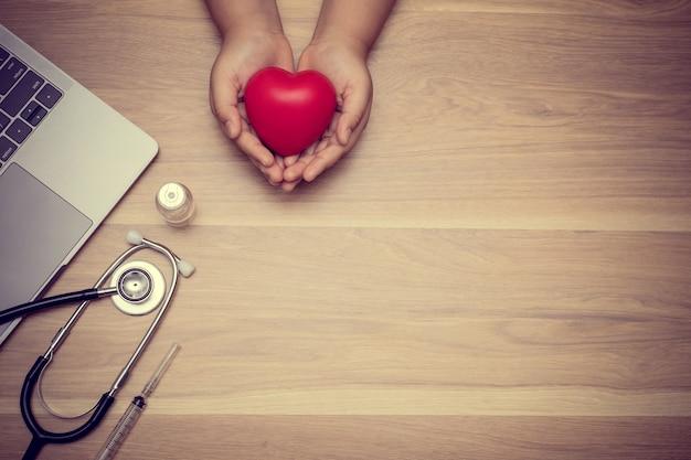 De dokter hield een rood hart op tafel met medische hulpmiddelen hartaanvalconcept