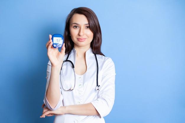 De dokter houdt een apparaat vast om de bloedsuikerspiegel te meten diabetes suikercontrole