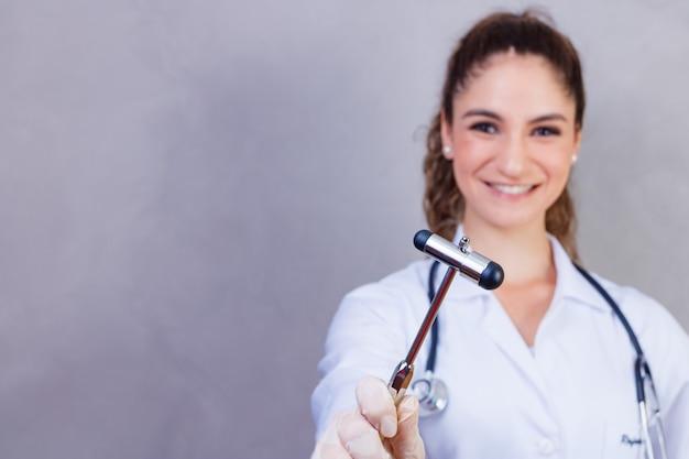 De dokter houdt een neurologische hamer op een grijze achtergrond. de neuroloog controleert de reflexen van de patiënt met een hamer. diagnostiek, gezondheidszorg en medische zorg