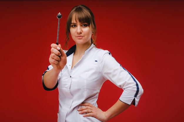 De dokter houdt een neurologische hamer op een rode achtergrond. de neuroloog controleert de reflexen van de patiënt met een hamer. diagnostiek, gezondheidszorg en medische zorg.
