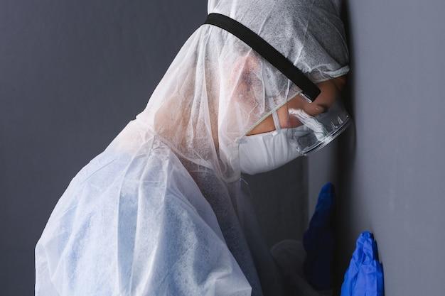De dokter in een beschermend pak met voorhoofd tegen de grijze muur vermoeidheid bij het bestrijden van het virus