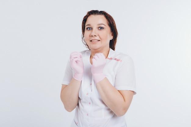 De dokter in rubberen handschoenen. een meisje draagt een beschermende uitrusting tijdens een epidemie. advertenties voor antiseptica en medische apparatuur op een witte achtergrond.