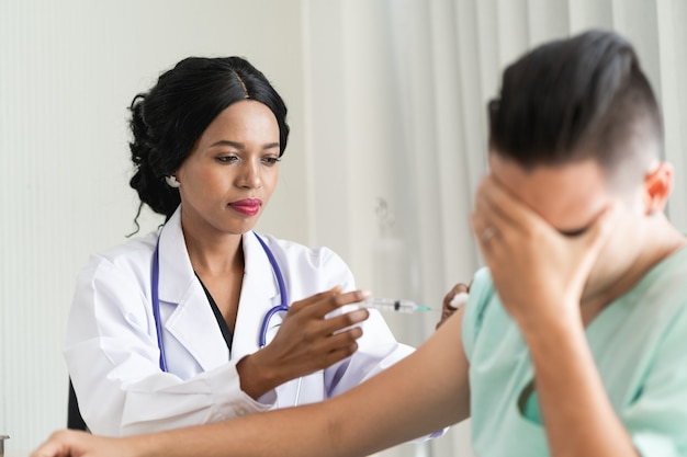 De dokter is aan het vaccineren tegen het corona virus. om de uitbraak van het corona virus te voorkomen
