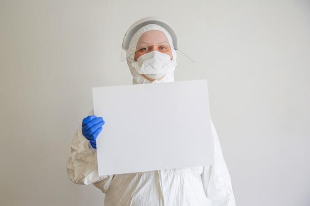De dokter is een vrouw van middelbare leeftijd met bril, beschermend pak en masker met een wit laken in haar hand