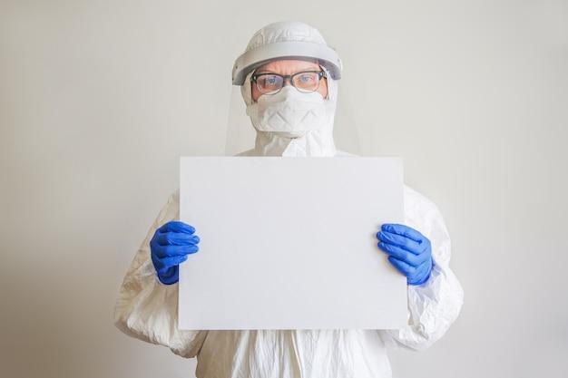 De dokter is een vrouw van middelbare leeftijd met bril, beschermend pak en masker met een wit laken in haar handen