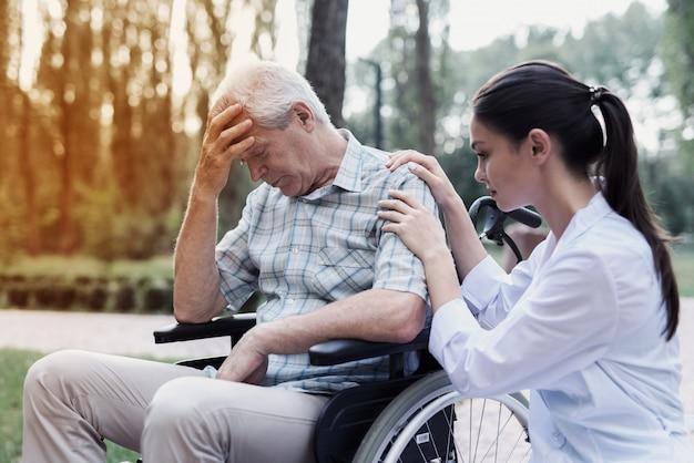 De dokter kalmeert de neerslachtige oude man in een rolstoel
