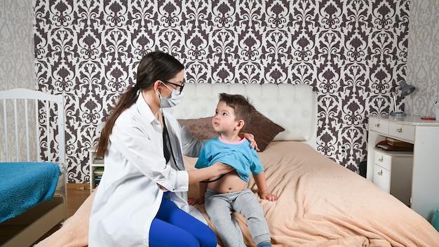 De dokter luistert naar het kind met een caleidoscoop.
