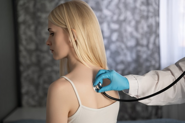 De dokter luistert of de longen goed werken. ze legde de stethoscoop op de rug.