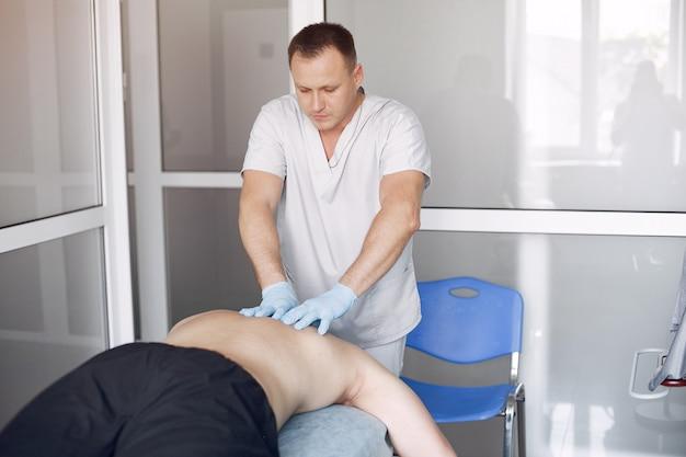 De dokter masseert de man in het ziekenhuis