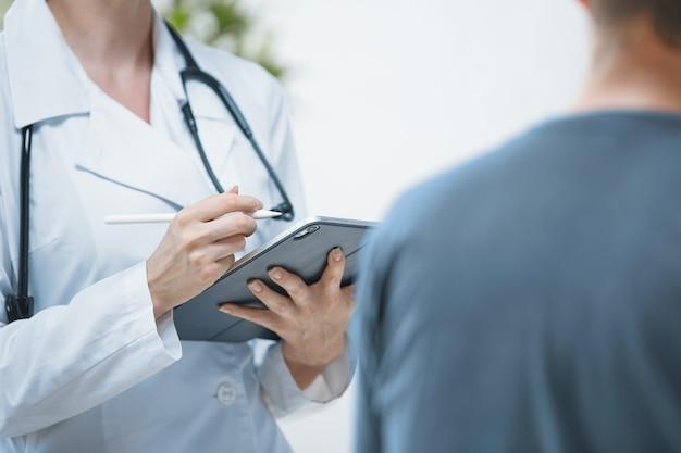 De dokter op kantoor voert een consult met de patiënt in een helder kantoor