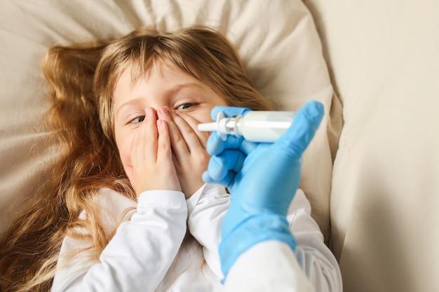 De dokter spuit een neusspray in de neus van het meisje