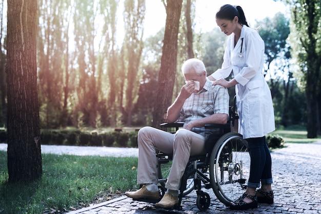 De dokter troost de huilende oude man in het zomerpark