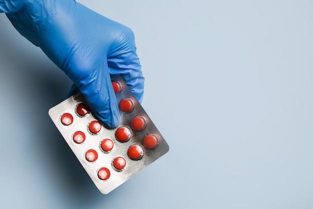 De doktoren dienen een blauwe beschermende handschoen in en houdt pillen in een blister