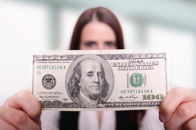 De dollar van de vrouwenholding voor haar gezicht.