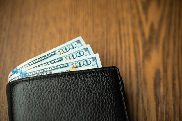 De dollars van verenigde staten papiergeld in zwarte portefeuille op houten lijstgebruik voor zaken, financiën.