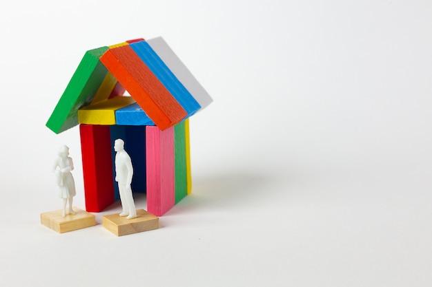 De domino-multikleur bouwt huis op witte achtergrond.