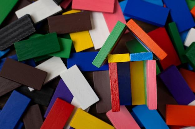 De domino-multikleur bouwt thuis op houten tafel.