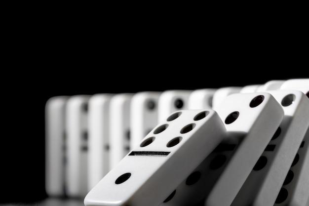 De dominostukken zetten op een rij op zwarte achtergrond