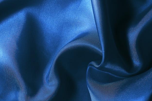 De donkerblauwe textuur van de stoffendoek voor het achtergrond en ontwerpkunstwerk