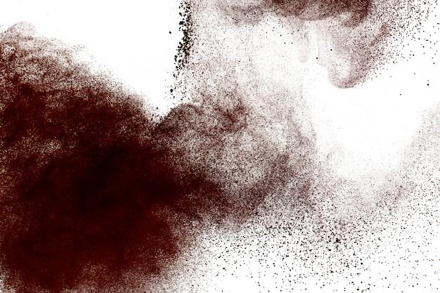 De donkerbruine explosie van het poederstof op witte achtergrond.