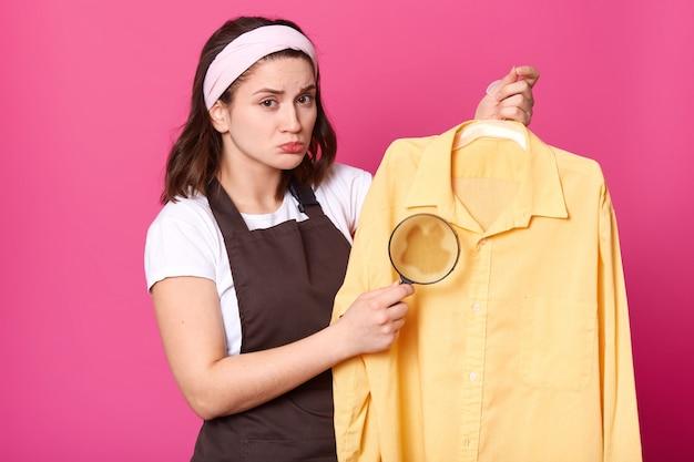De donkerbruine huisvrouw houdt geel overhemd na was met koffievlek op stof, met vergrootglas in één hand. emotioneel schattig jong model met bruine schort, wit t-shirt en hoofdband.