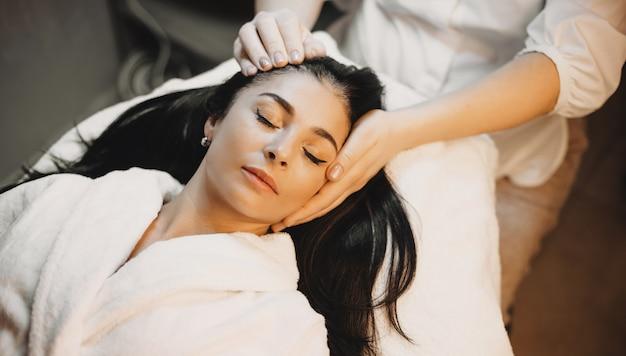 De donkerbruine kaukasische dame ligt en heeft een hoofdmassageprocedure in een professionele kuuroordsalon
